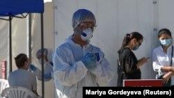 Медицинский работник в защитной одежде в пункте тестирования на коронавирус. Алматы, 8 июля 2020 года.