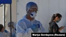 Медработник в защитной одежде в центре тестирования на COVID-19. Алматы, 8 июля 2020 года.