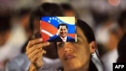 Женщина держит фото Уго Чавеса на церемонии в поддержку его здоровья. Никарагуа, 9 декабря 2012 года.