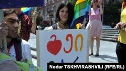 """Мне запомнилась одна из них: привлекательная девушка с открытым чистым лицом идет под радужным флагом. В руках квадратная табличка с нарисованным сердцем и разноцветными грузинскими литерами. «Там написано """"я – гей"""", - поясняет грузинский блогер и издеват"""