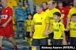 Аким Алматы Ахметжан Есимов (в центре) и другие игроки из раздевалки вышли, держа за руку юных футболистов. Алматы, 26 сентября 2012 года.
