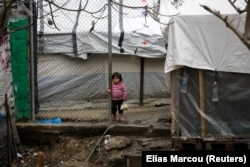 Një vajzë migrante, qëndron pranë një kampi në Lesbos të Greqisë. Fotografi nga arkivi.