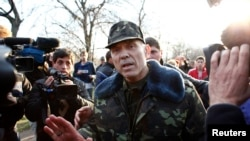 Ukrainian General Vasyl Krutov (center) talks to journalists in front of the airbase in Kramatorsk in eastern Ukraine on April 15.