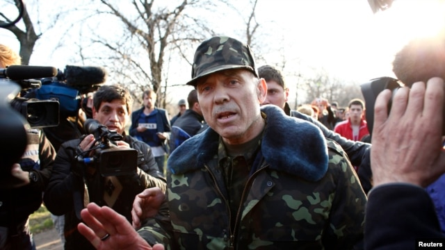 Ukrainian General Vasyl Krutov (center) talks to journalists in front of the air base in Kramatorsk in eastern Ukraine on April 15.