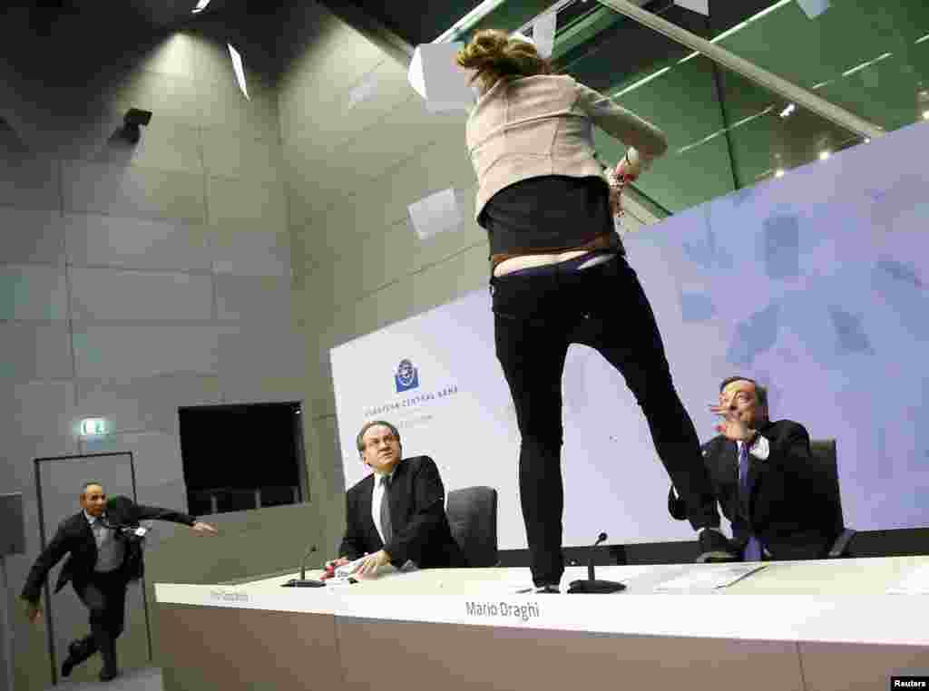 "A protester jumps on the table in front of European Central Bank President Mario Draghi during a news conference in Frankfurt. The protester screamed ""End ECB dictatorship"" and threw confetti. Security agents dragged the woman off the stage. (Reuters/Kai Pfaffenbach)"
