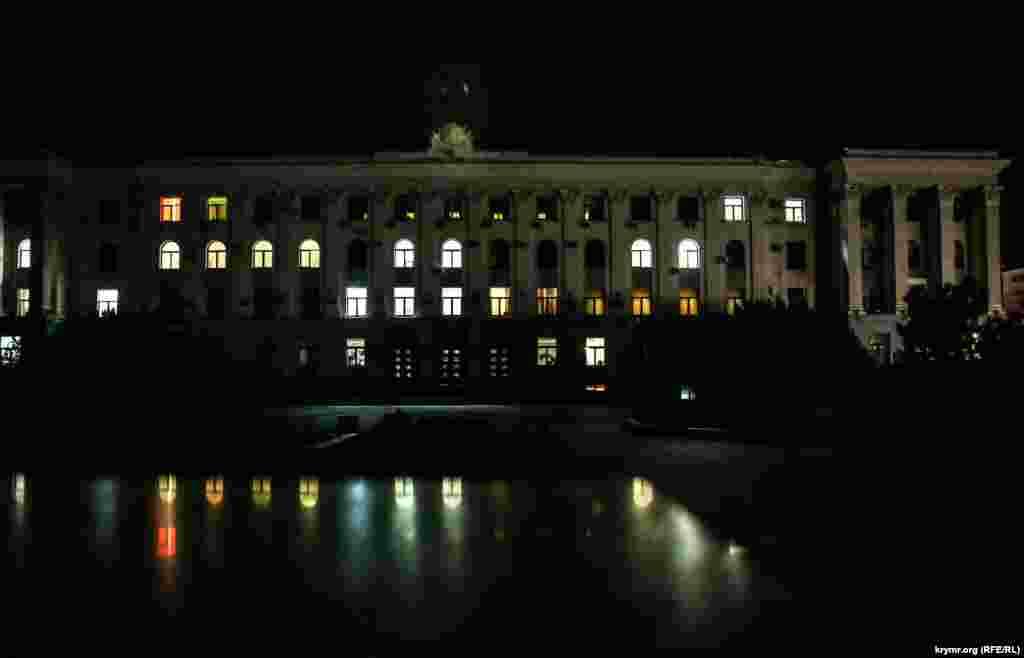 В окнах правительственного здания после наступления темноты горит свет.