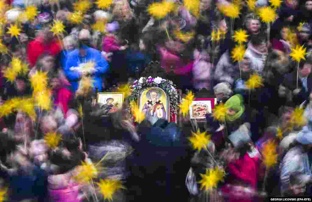Young children holding sticks decorated with stars walk around religious icons on the eve of Orthodox Christmas in the St. Kliment Central Orthodox Church in Skopje, North Macedonia. (epa-EFE/Georgi Licovski)