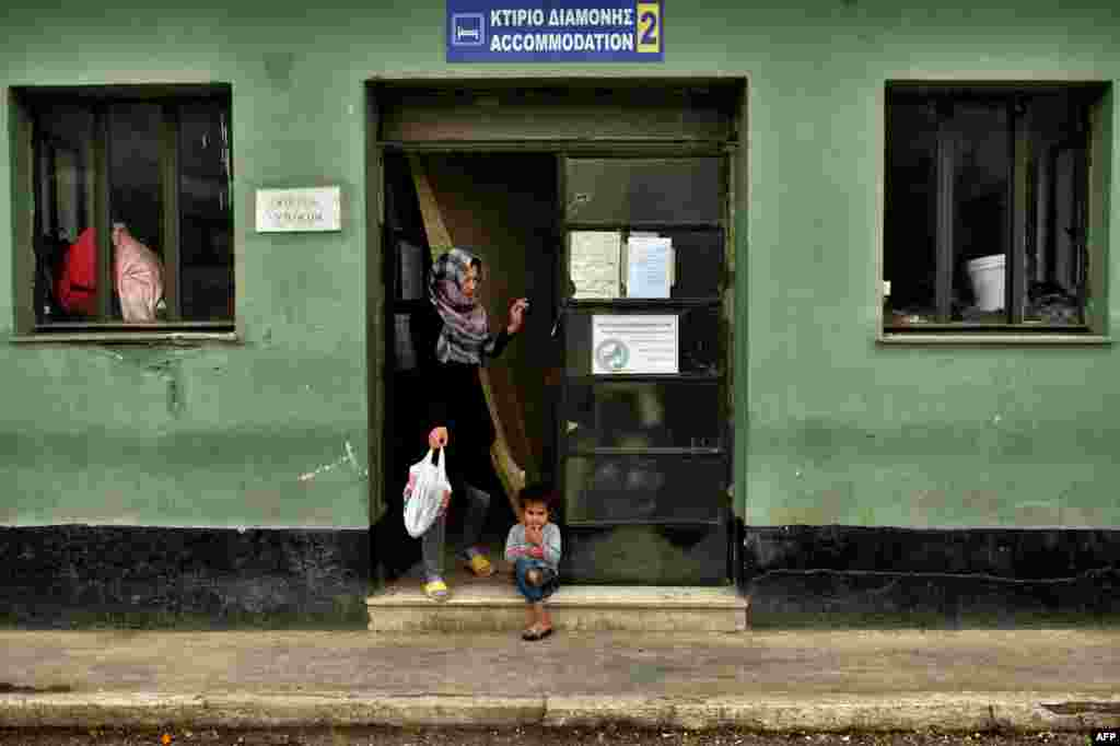 A child sits at the entrance of a building at the refugee camp of Schisto in Athens, Greece. (AFP/Aris Messinis)