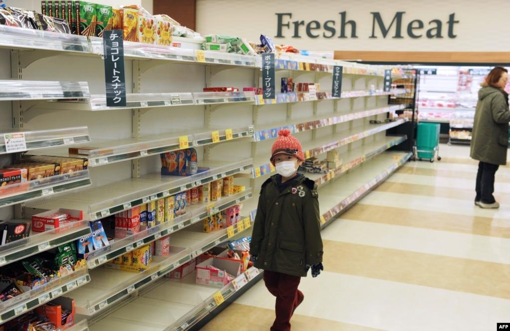 Хлопчик у масці проходить повз напівпорожні полиці супермаркету на північному заході Японії, в місті Акіта, 15 березня 2011 року. Після землетрусу з цунамі і ядерної кризи людей охопила паніка. Того дня на АЕС «Фукусіма-1» сталися ще два вибухи водню і сильна пожежа, що призвело до значних викидів радіації