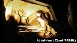 الفنان أمجد شاكر ينفذ إحدى لوحاته
