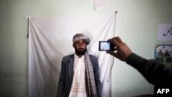 Пришедшего за карточкой избирателя фотографирует сотрудник регистрационного центра. Герат, 31 марта 2014 года.