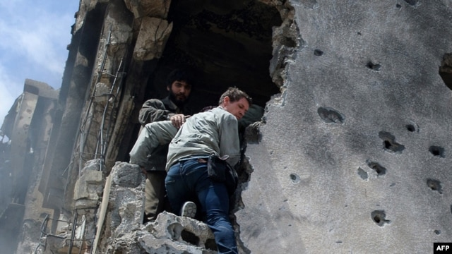 A photograph shortly before he was killed shows Tim Hetherington (center) being assisted by rebels as he climbs down a building after gunshots rang out in the besieged Libyan city of Misurata on April 20.
