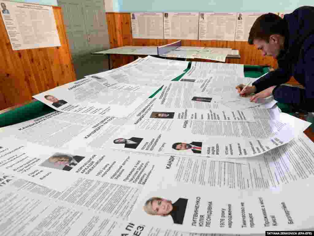 An election observer signs a protocol during the Ukrainian presidential elections in the village of Velyki Dmytrovychi, some 40 km south of Kyiv. (EPA-EFE / Tatyana Zenkovich)