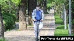 Маска таққан ер адам самокат айдап барады. Алматы, 25 сәуір 2020 жыл.