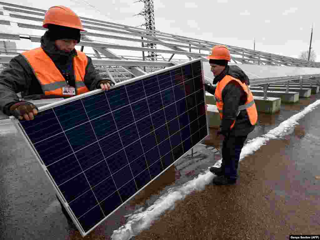 "Workers wrestle one of the new Chernobyl project's 3,800 solar panels into position. The Ukrainian-German company behind the project told AFP on January 10 that the solar plant will generate enough electricity to power ""a large village,"" or around 2,000 apartments."