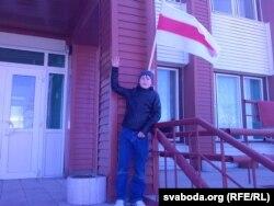 Вітаўт Яжэвіч пад вывешаным на будынку школы сьцягам.