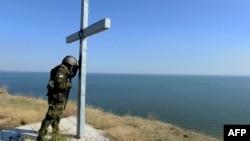 Украинский военнослужащий молится у креста, установленного на берегу моря близ города Мариуполя. Октябрь 2014 года.