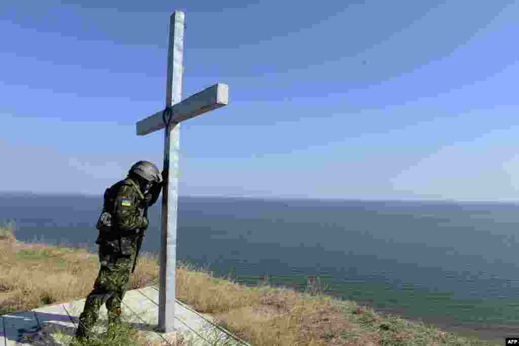 A soldier of the pro-Ukrainian St. Maria Battalion prays at a cross installed above the sea near the eastern city of Mariupol. (AFP/Alexander Khudoteply)