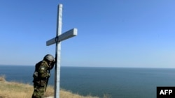 A Ukrainian serviceman prays by a cross outside the eastern city of Mariupol, a port of crucial economic importance on the Azov Sea.
