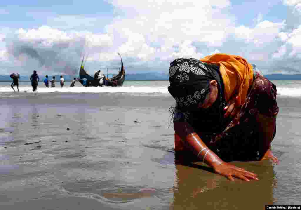 An exhausted Rohingya refugee woman touches the shore after crossing the Bangladesh-Myanmar border by boat through the Bay of Bengal in Shah Porir Dwip, Bangladesh, September 11, 2017. (Reuters/Danish Siddiqui)