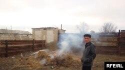 Қаза тапқан Дарханның әкесі Манарбек Олжағалиев қылмыс болған жерді көрсетіп тұр. Бала бақша меңгерушісі Дарханның денесі табылған жердегі қоқысты өртеп жатыр. Ақжар ауылы, 14наурыз, 2009 жыл.