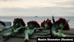 Цветы на пристани на фоне корабля МЧС, задействованного в поисковой операции в Черном море после крушения военного самолета Ту-154. 26 декабря 2016 года.