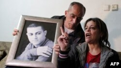 The parents of 19-year-old Muhammad Musallam (shown in the portrait) react to the news of his reported killing at the family's home in the East Jerusalem Jewish settlement of Neve-Yaakov.