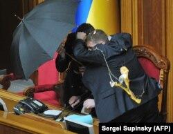 Володимира Литвина, голову Верховної Ради, прикривають парасольками під час голосування за «Харківські угоди»