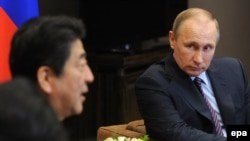 Russian President Vladimir Putin (right) and Japanese Prime Minister Shinzo Abe talk during their meeting in Sochi on May 6.