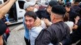 Полицейские задерживают мужчину во время митинга в Алматы в день президентских выборов. 9 июня 2019 года.