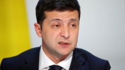 """Ukraine's President Volodymyr Zelenskiy speaks during a press conference after the Paris summit. Activists in Ukraine says Zelenskiy crossed no """"red lines"""" in his talks with Putin."""