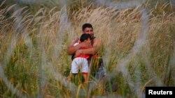 Біженець із дитиною на сербському боці угорсько-сербського кордону, 15 вересня 2015 року