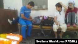 Медик осматривает одну из участниц голодовки в доме Алтын Червалиевой, который собираются снести. Астана, 8 августа 2014 года.