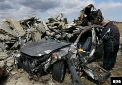 Пожилой японец молится о погибшем сыне у остова автомашины, в которой тот погиб во время цунами