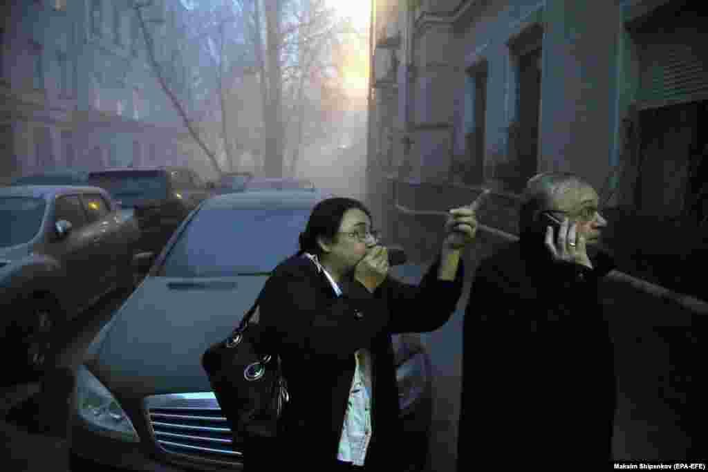 Людзі рэагуюць на нечаканы развал шасьціпавярховага будынка ў цэнтры Масквы, дзе ішоў рамонт. Ахвяраў не было, бо адбылася эвакуацыя рабочых і жыхароў суседніх дамоў. (epa-EFE/Maksim Shipenkov)