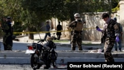 Afghan security forces inspect the site of a suicide attack in Kabul on September 9