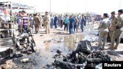 مواطنون وقوات أمن في مكان تفجير سيارة مفخخة في الكوت