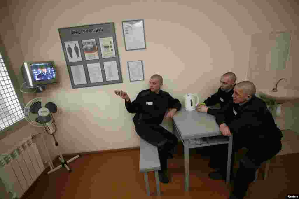 Inmates watch TV inside a temporary cell for recently arrived prisoners.