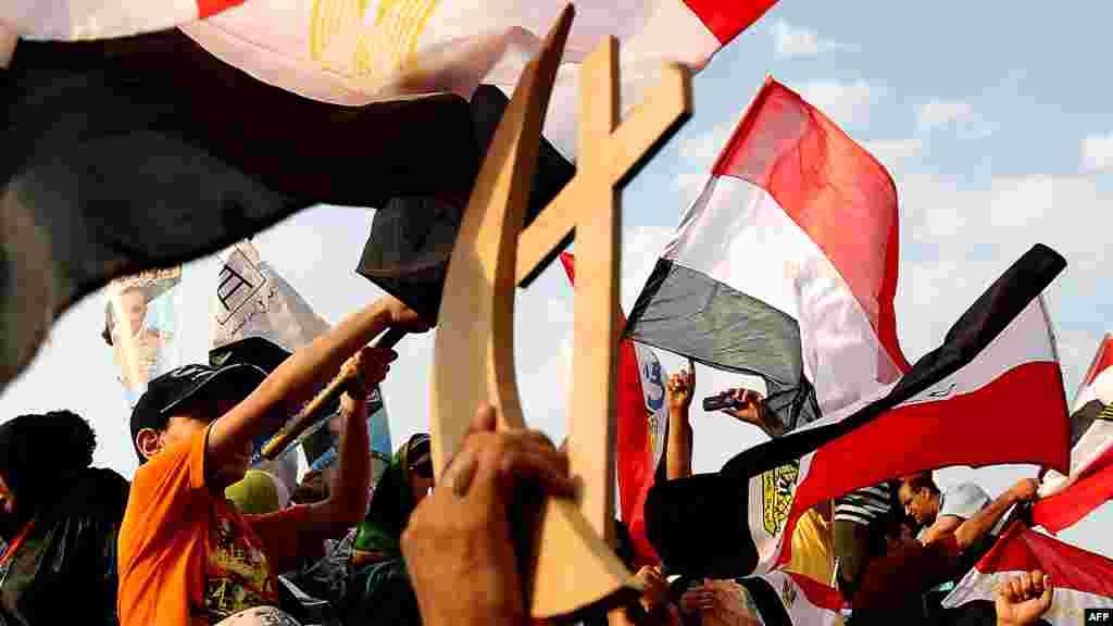 Ахмед Шафиктің қолдаушылары христиан белгісі крест пен мұсылман символы жарты айды біріктіре ұстап тұр. Каир шетіндегі Наср ауылы, 23 маусым 2012 жыл