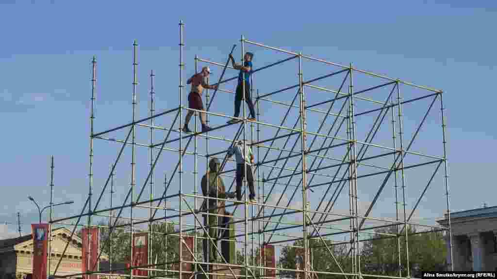 Робітники збирають сцену на площі Леніна