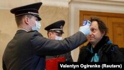 Un ofițer de la Departamentul de pază verifică temperatura unui jurnalist la intrarea în palatul prezidențial din Kiev