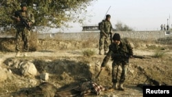 An Afghan soldier pulls belongings from an insurgent, dressed in army uniform, after an attack at the Jalalabad airport.