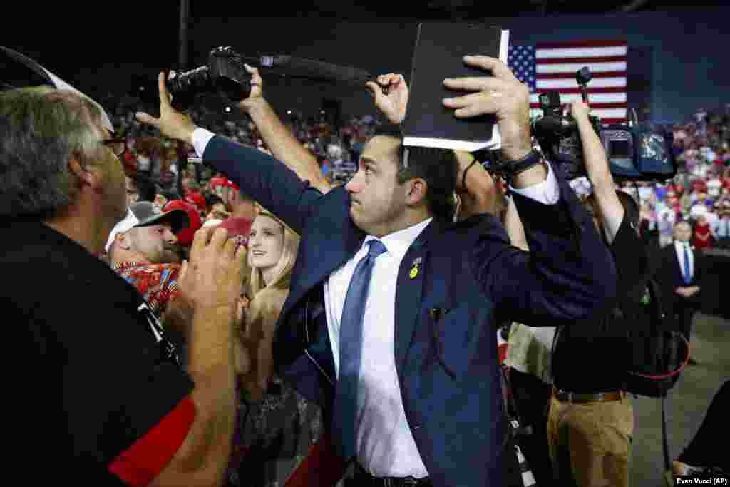 A volunteer member of the advance team for U.S. President Donald Trump blocks a camera with his hand as a photojournalist attempts to take a photo of a protester during a campaign rally in Evansville, Indiana, on August 30. (AP/Evan Vucci)