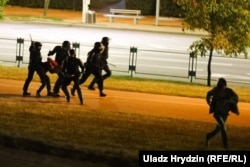 Riot police beat a group of people while another attempts to flee on August 11-12.