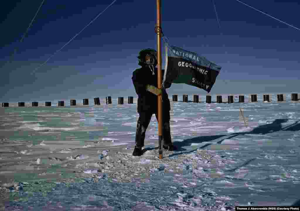 """National Geographic"" magazine's Thomas Abercrombie, the first correspondent to reach the South Pole, in 1957, flies the society's flag from the pole while reporting on the International Geophysical Year of 1957-58."