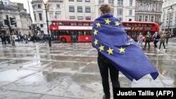 Участник демонстрации, укутанный в флаг Евросоюза, покидает акцию против выхода Великобритании из Евросоюза. 28 июня 2016 года.