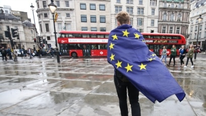 A demonstrator wrapped in a European flag leaves an anti-Brexit protest