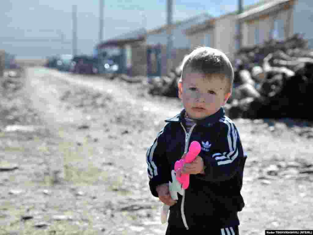 ახალსოფელში მცხოვრები დევნილი ბავშვი - 2008 წლის აგვისტოს ომის შემდეგ შექმნილ დევნილთა დასახლებებს რამდენიმე საერთაშორისო და ადგილობრივი ორგანიზაცია ეხმარება.