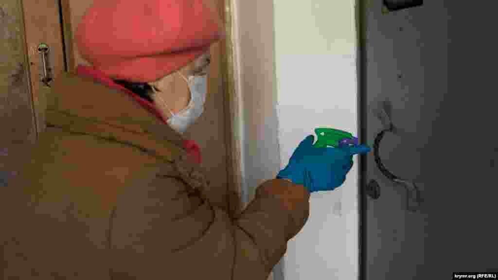 Працівниця ЖЕКу дезінфікує дверні ручки в під'їзді багатоповерхівки одного зі спальних районів кримської столиці