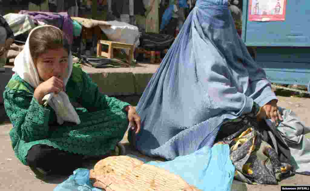 Women sell traditional bread by the side of the road.